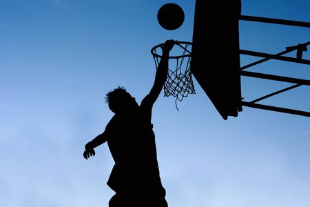effort: silhouette of basketball player and hoop against deep blue sky Stock Photo