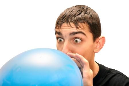 Teenager inflating big blue balloon. Isolated.