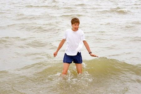 hydrophobia: scared teenager stand in the middle of the water