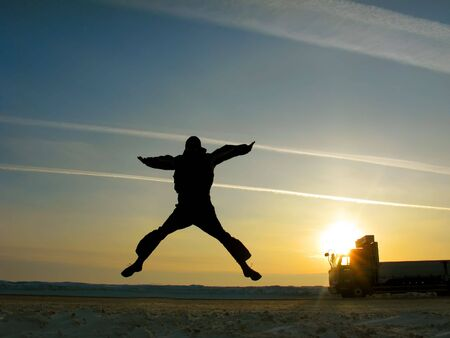 happy man jumping on the sunset sky background  photo