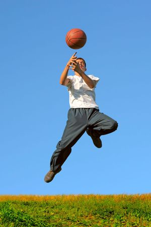 a boy dribbling a basketball in a game photo