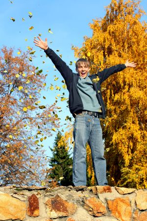 happy teenager scatter leafs in the autumn park Stock Photo - 5652626