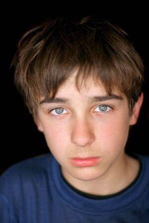 sad teenager portrait on the black background photo
