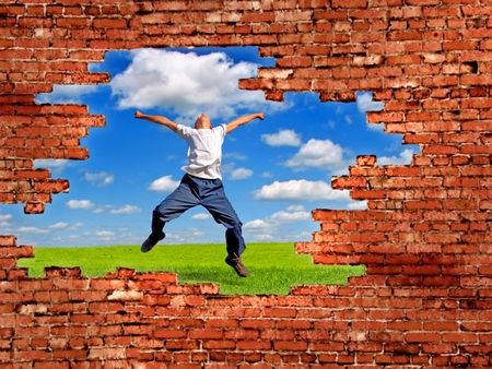 hole in the brick wall on the view of landscape with teenager jumping photo
