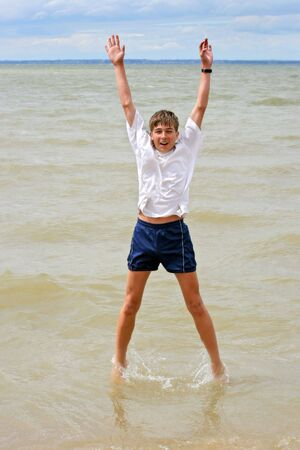 happy teenager jumping in the water photo