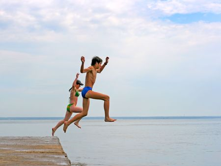 two happy teenagers jumping in the sea