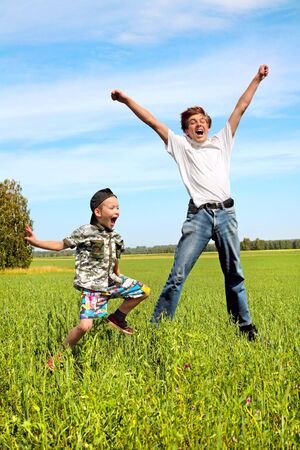 Happy teenager and kid jumping on the meadow Stock Photo - 5909527