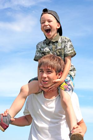 The happy child sits on the teenager shoulders photo