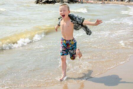 The happy child runs on seacoast photo