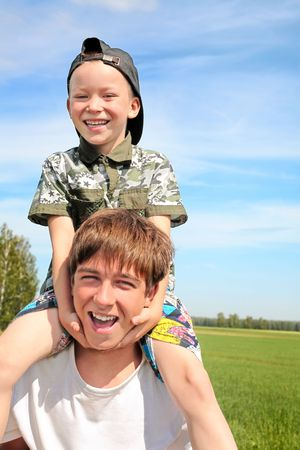 The happy child sits on the teenager shoulders Stock Photo - 6433428