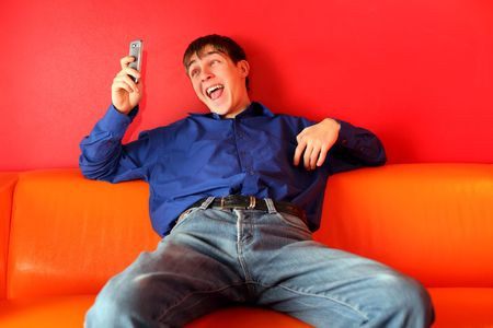 playing on divan: teenager get funny sms on the phone Stock Photo