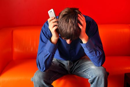 sad teenager sitting on the sofa with the mobile phone Stock Photo - 6433398