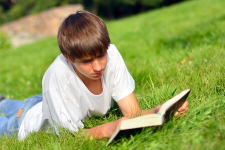The teenager reads the book on a summer meadow photo
