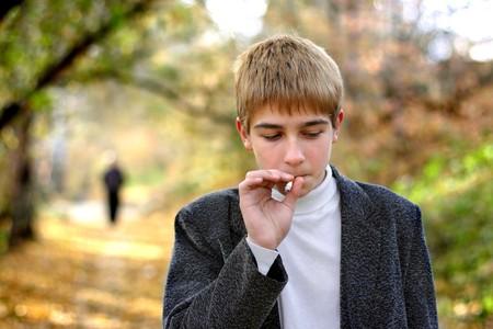 joven fumando: problema adolescente fumar cigarrillos en el Parque Foto de archivo