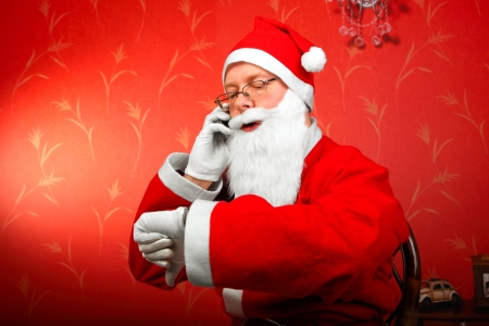 santa claus talking on mobile phone and looking on the watch