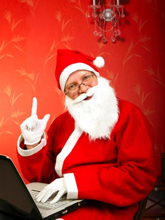 santa claus with notebook and finger up photo
