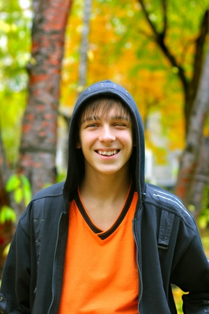 smiling teenager stand in the autumn park photo