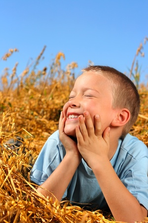 happy young boy in the wheat field photo