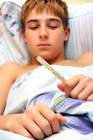 ailment: Sick teenager laying in bed with focus on thermometer Stock Photo