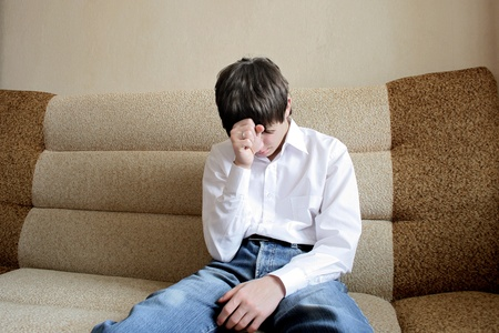 mirada triste: adolescente triste sentado en el sof�