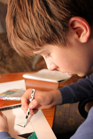 The boy doing lessons and with concentration drawing photo