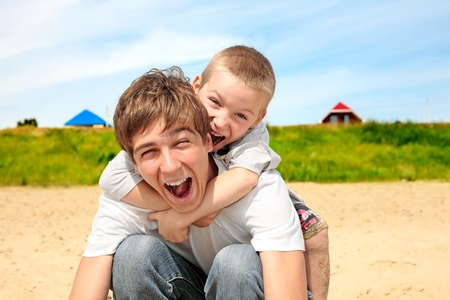 bros: happy teenager and kid on the beach Stock Photo