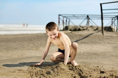 young boy playing in the sand photo