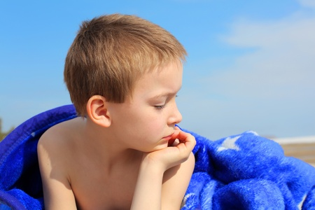 lying on side: pensive boy lying on the beach under blanket