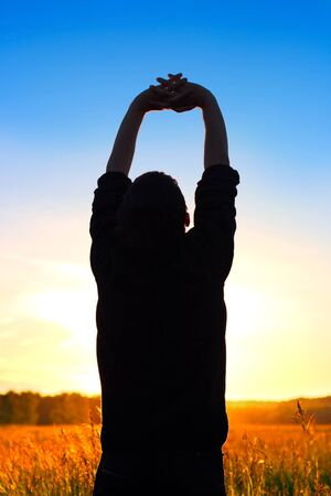 man silhouette with hand up on sunset background Stock Photo - 9872208