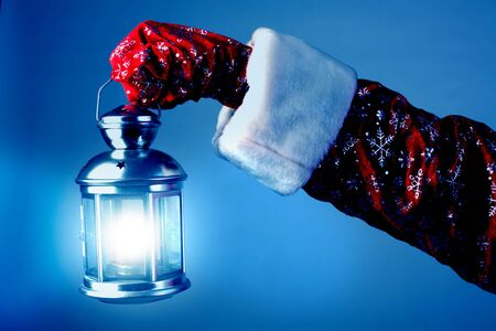 The hand of Santa Claus holds a lamp photo