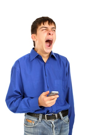 wearied: yawning teenager with mobile phone isolated on the white