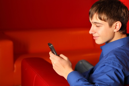 playing on divan: smiling teenager in the room with mobile phone