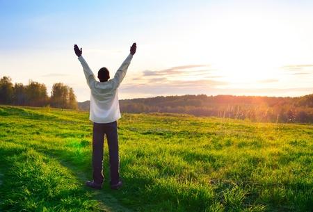 orando manos: silueta de hombre orante sobre fondo sunset