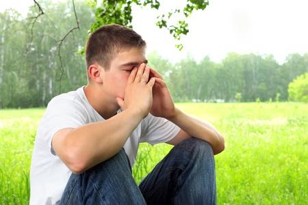 hombre solo: adolescente triste sentado en el bosque por s� solo