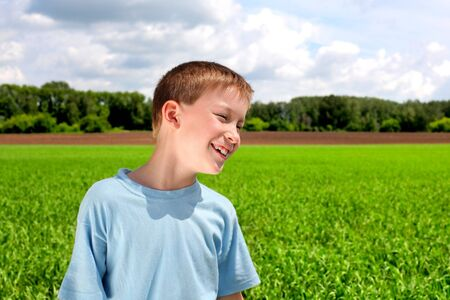 see side: happy boy in the summer field