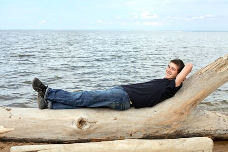 happy young man resting against seaside background