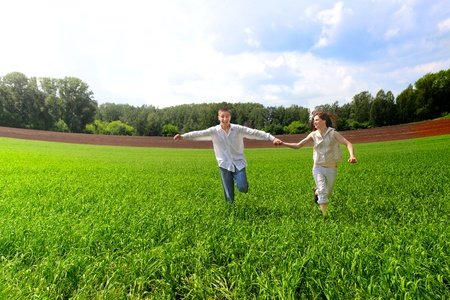 happy couples running in the summer field photo