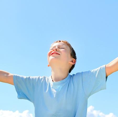 happy boy on the blue sky background Stock Photo