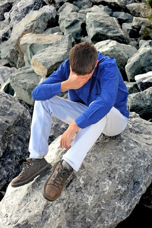 sad teenager sitting on the rocks photo