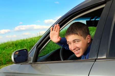 happy young man sitting in the car and wave goodbye Stock Photo - 11221128