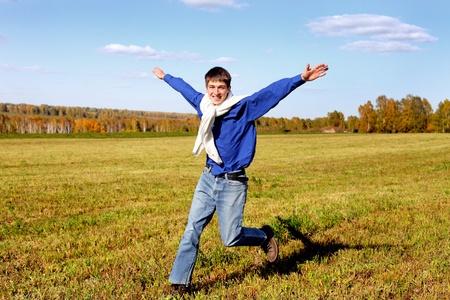 happy teenager running on the autumn field photo