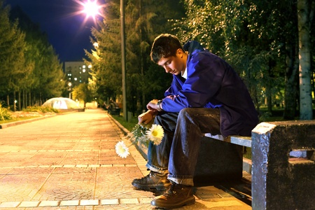 first date: teenager with flowers sitting in the night park and looking on the watch Stock Photo