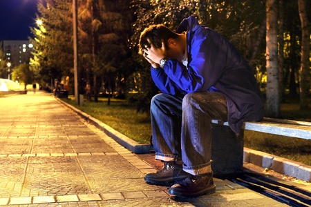 sad and lonely teenager with hidden face sitting in the night park Stock Photo