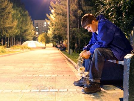 homme triste: Adolescent triste avec des fleurs d'attente pour une fille. concept de rendez infructueuses