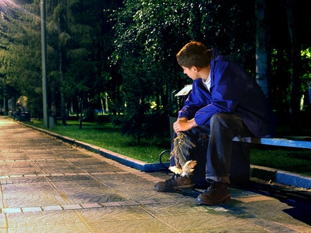 unhappy man: sad teenager in the night park with flowers