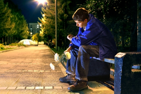 teenager in the evening park in expectation of girlfriend looking on the watch photo