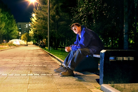 boy alone: lonely teenager sitting in the night park alone