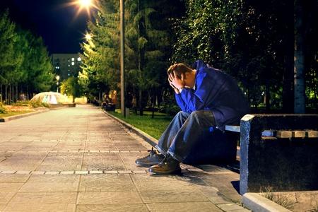 verontruste tiener met verborgen gezicht zit in de nacht park Stockfoto