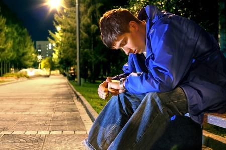 mirada triste: adolescente sentado en la noche del parque callej�n y mirando el reloj Foto de archivo
