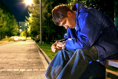 teenager sitting in the night park alley and looking on the watch